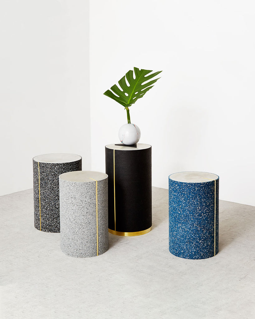 Four round side tables in speckled black, speckled gray, speckled blue and black rubber with concrete table top.