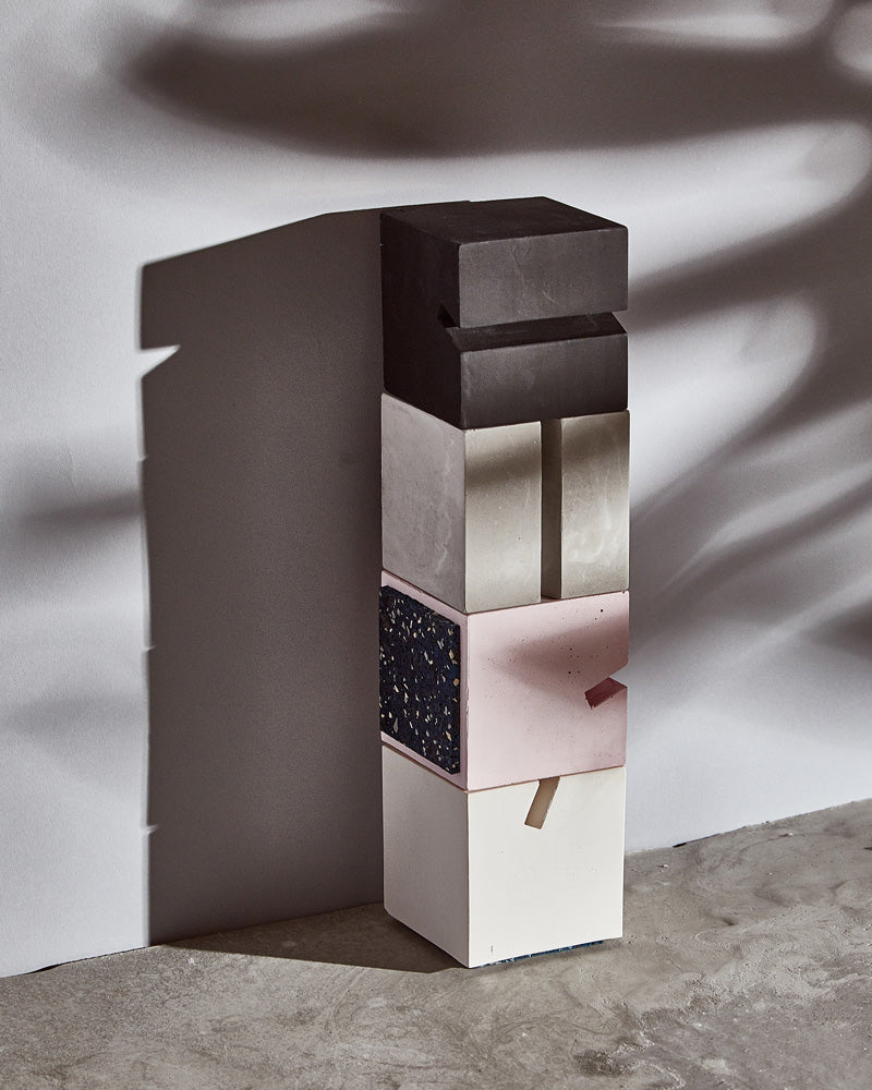 Black, grey, pink, white cube card holders stacked up on concrete surface.