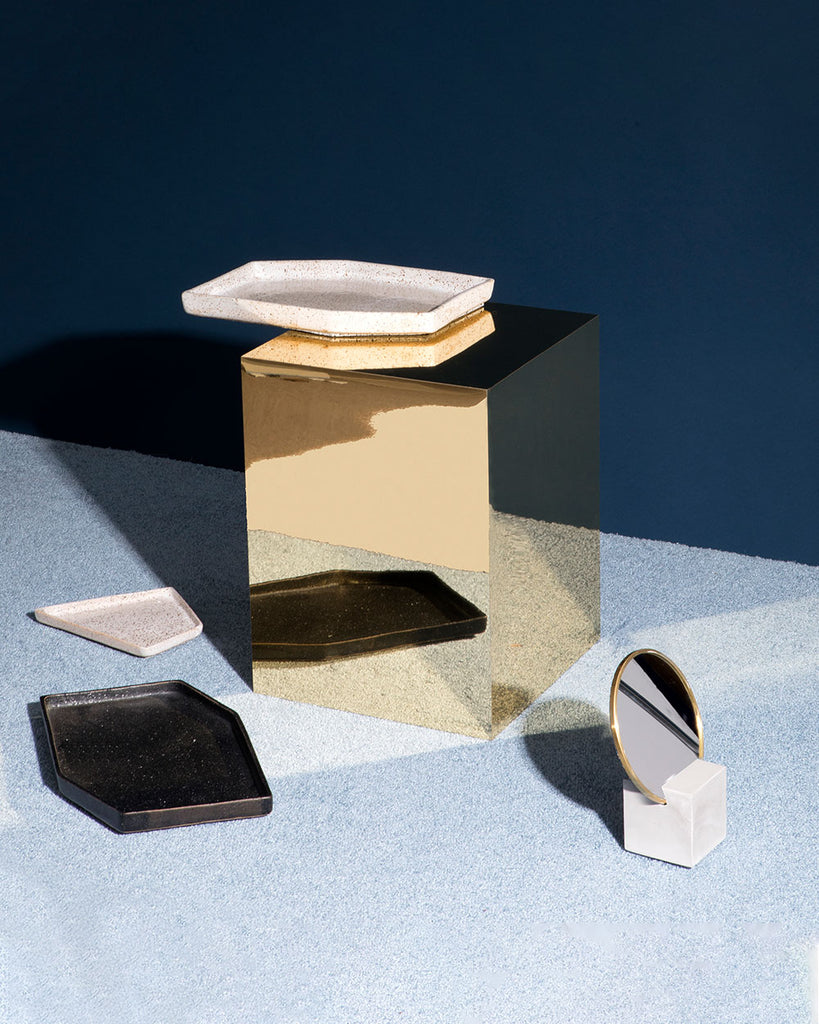 Ceramic nesting tray on shiny brass rectangular side table. White cube base brass ring vanity mirror and black nesting tray on blue carpet.