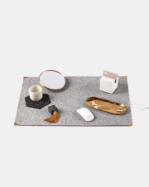 Rectangle speckled grey rubber desk mat with brass corners. Desk mat is styled with white cube card holder, round brass frame mirror, white mouse, brass oval tray with headphones, hexagon speckled black trivet with white espresso cup and speckled black rubber tassel.