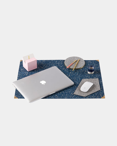 Rectangle speckled blue rubber desk mat with brass corners. Desk mat is styled with pink cube card holder, round brass speckled grey rubber trivet with pen, white mouse on grey speckled gem mousepad. blue espresso cup and MacBook laptop.