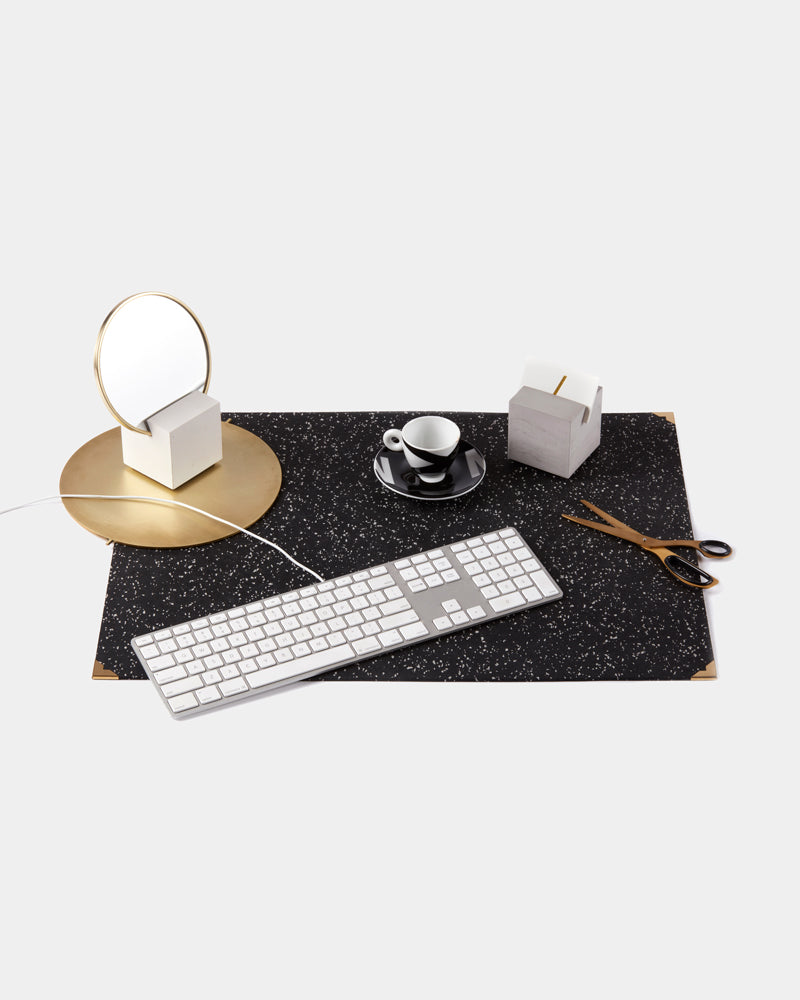 Rectangle speckled blue rubber desk mat with brass corners. Desk mat is styled with grey cube card holder, round brass trivet with white cube base vanity mirror, black espresso cup, brass scissors and white keyboard.