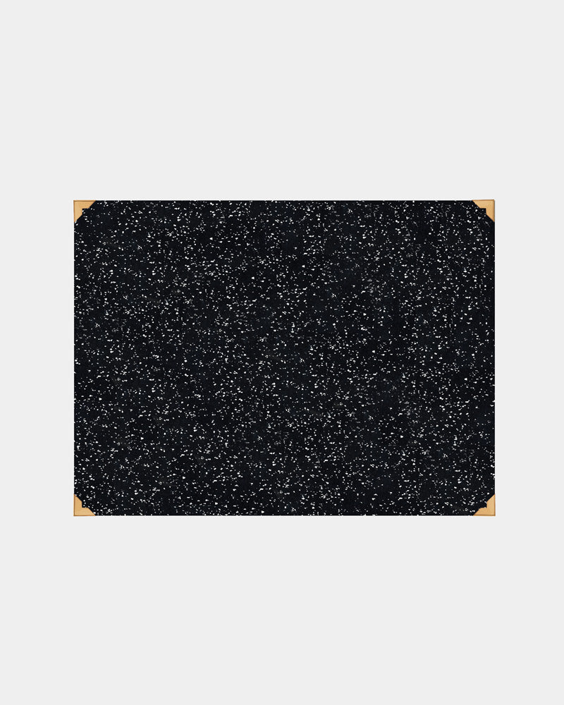 Rectangle speckled black rubber desk mat with brass corners on white background.