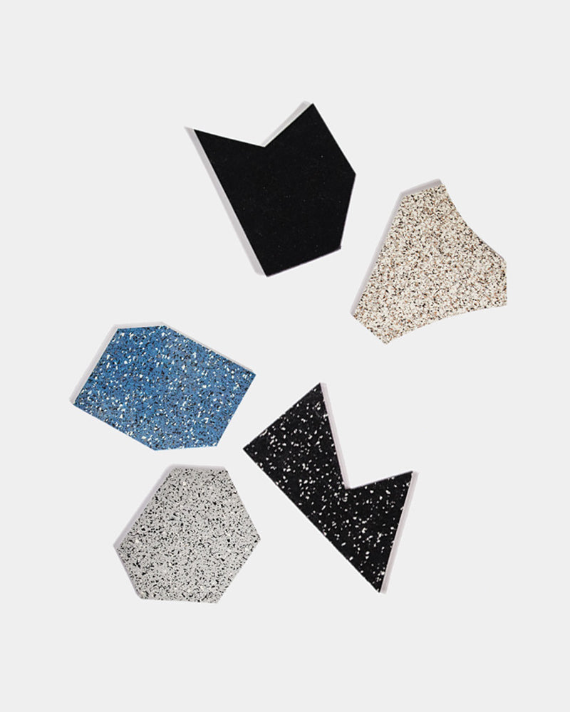 Gem rubber shapes in speckled beige, speckled blue, speckled grey, speckled black and pure black color. Scattered around on white surface.