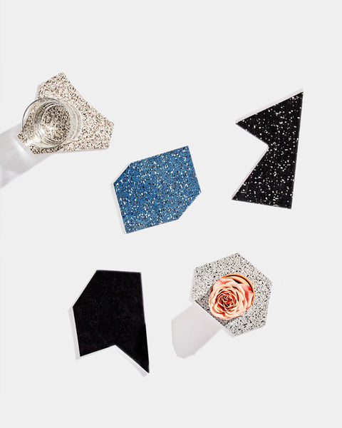 Gem rubber shapes in speckled beige, speckled blue, speckled grey, speckled black and pure black color. Scattered around on white surface. Grey rubber has rose and beige rubber has glass with water on its surface.