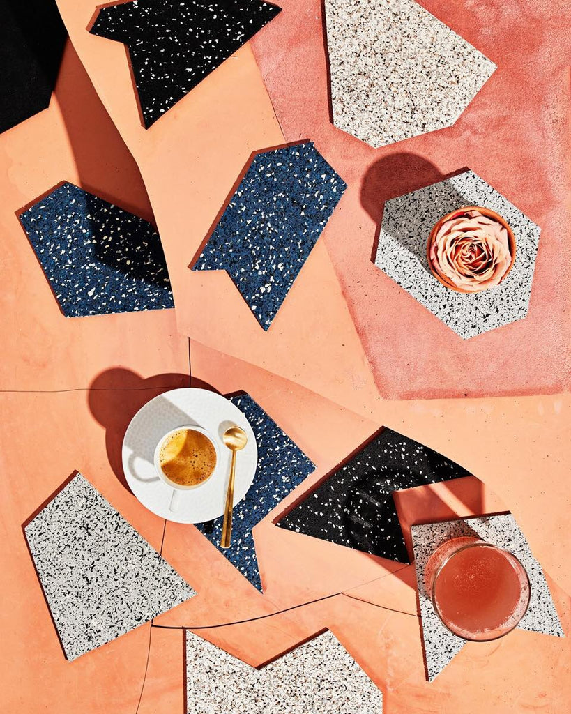 Gem rubber shapes in speckled beige, speckled blue, speckled grey, speckled black nd pure black color. Scattered around on terracotta colored surface. The gem rubbers are styled with espresso cup with coffee, glass with orange juice and rose.