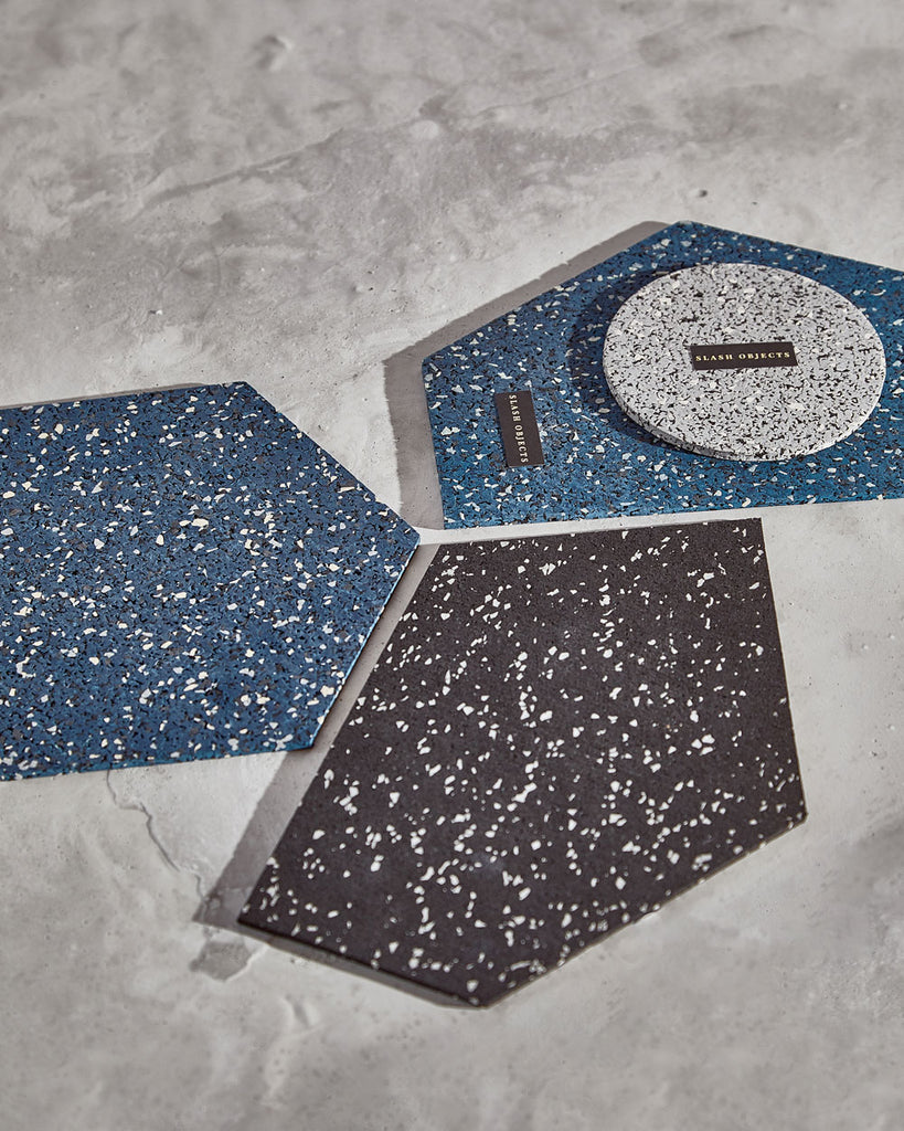 Rubber gem mousepad in speckled black and speckled blue and hexagon speckled blue rubber trivet on concrete surface.