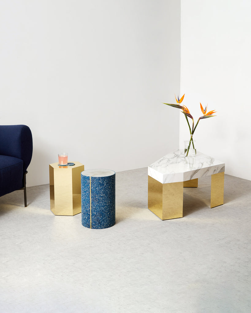 Marble and brass gem coffee table, speckled blue rubber CYL side table and brass hexagon side table on concrete surface.