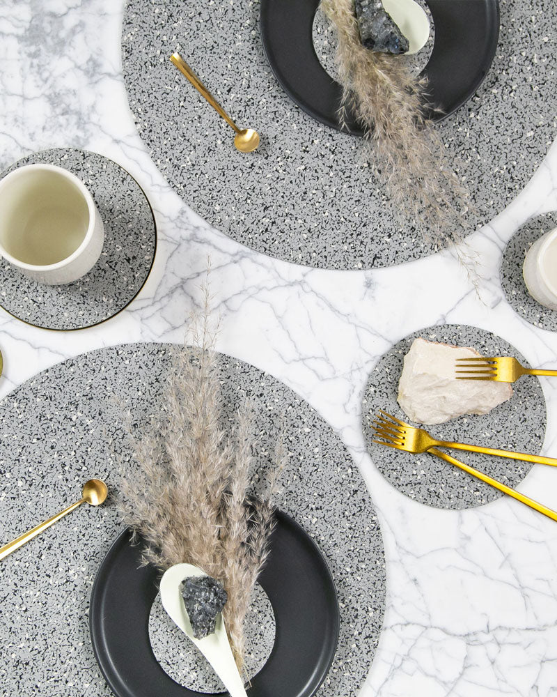 Speckled grey table setting with round placemats and round trivet styled with brass cutlery, rocks, espresso cup, dark grey plates and pampas plant.