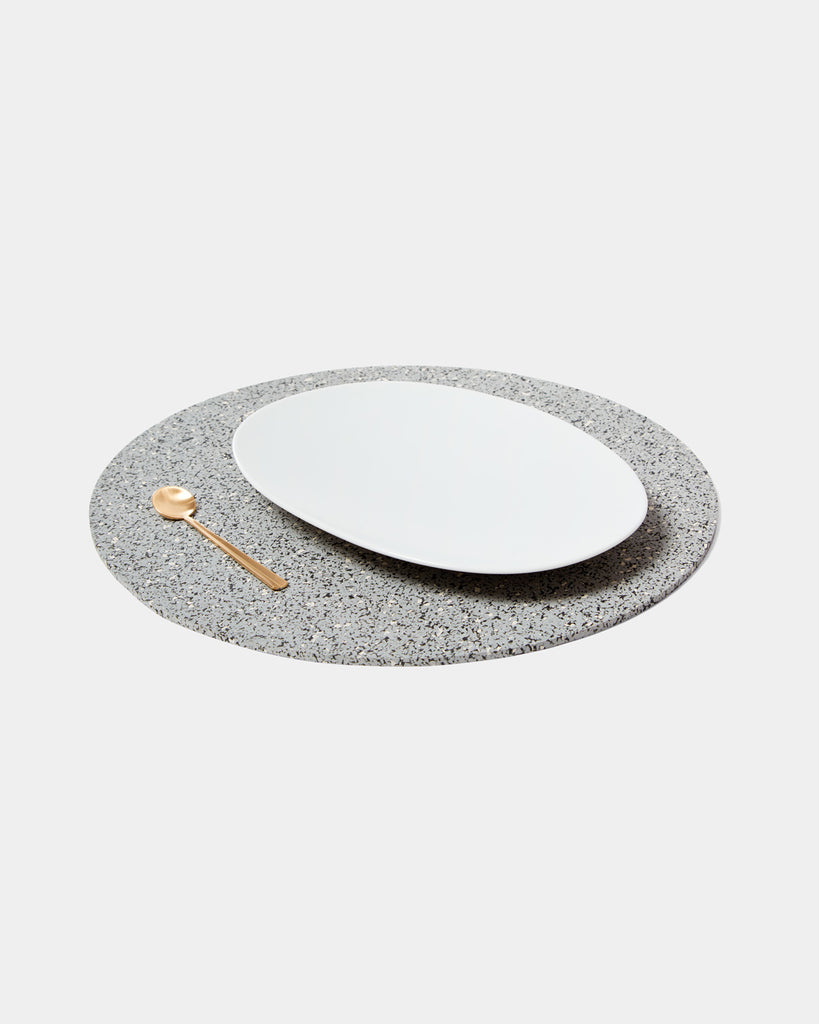 Speckled grey round placemat with white place and brass spoon on white surface.