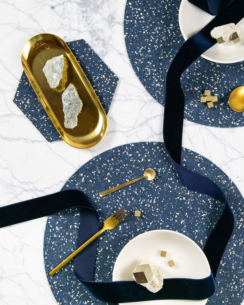 Speckled blue table setting with round placemats and hexagon trivet styled with brass cutlery, brass tray rocks, white plates and dark blue ribbon.