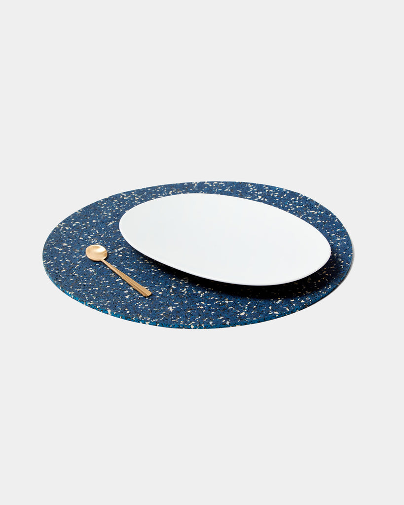 Speckled blue round placemat with white place and brass spoon on white surface.