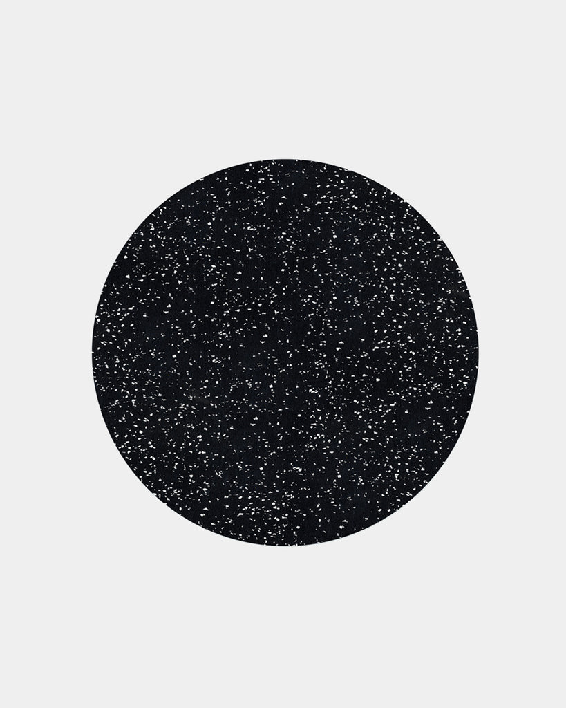 Speckled black round placemat on white surface.