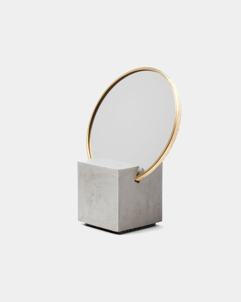 Front view of vanity mirror with grey cube base and round brass mirror frame on white background.