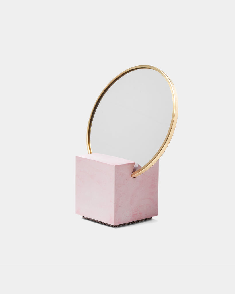 Front view of vanity mirror with pink cube base and round brass mirror frame on white background.
