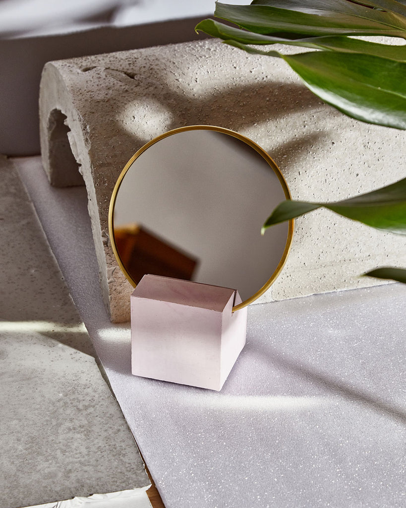 Lifestyle image of vanity mirror with pink cube base and round brass mirror frame in front of concrete sculpture. Green plant leaves overlapping the mirror on the top right corner.