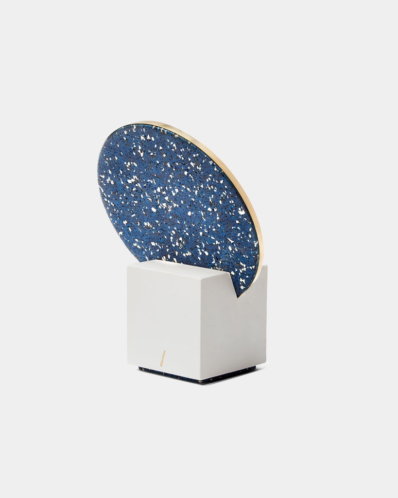 Back view of vanity mirror with white cube base and round brass mirror frame, speckled blue rubber back on white background.