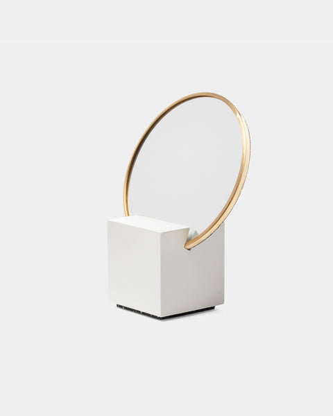Vanity Mirror with white cube base and round brass mirror frame on white background.