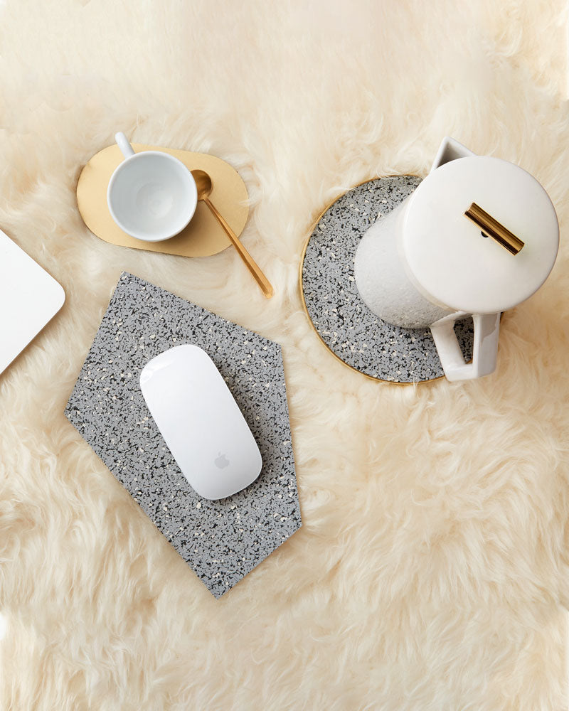 Geometric gem shaped speckled grey rubber mousepad with a white mouse, round brass and speckled grey trivet with white french press and brass oval coaster with white espresso cup and brass spoon on beige fur surface.