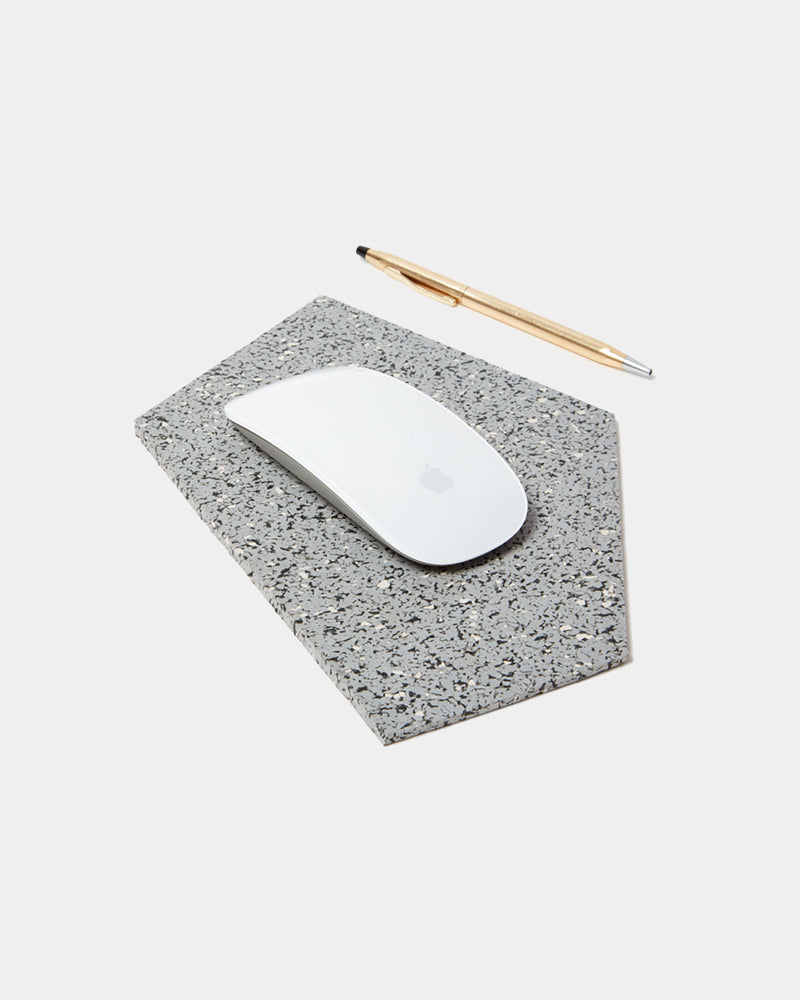 Geometric gem shaped speckled grey rubber mousepad with a white mouse and brass pen on white background.