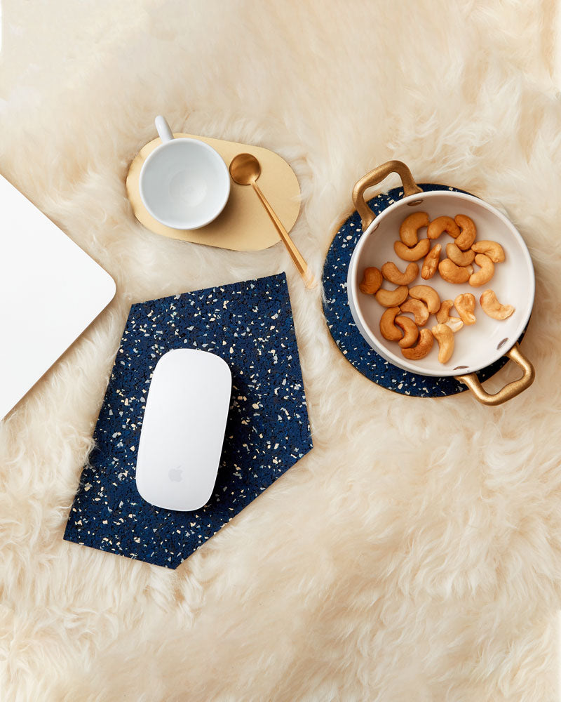 Geometric gem shaped speckled blue rubber mousepad with a white mouse, round brass and speckled blue trivet with small pan and brass oval coaster with white espresso cup and brass spoon on beige fur surface.
