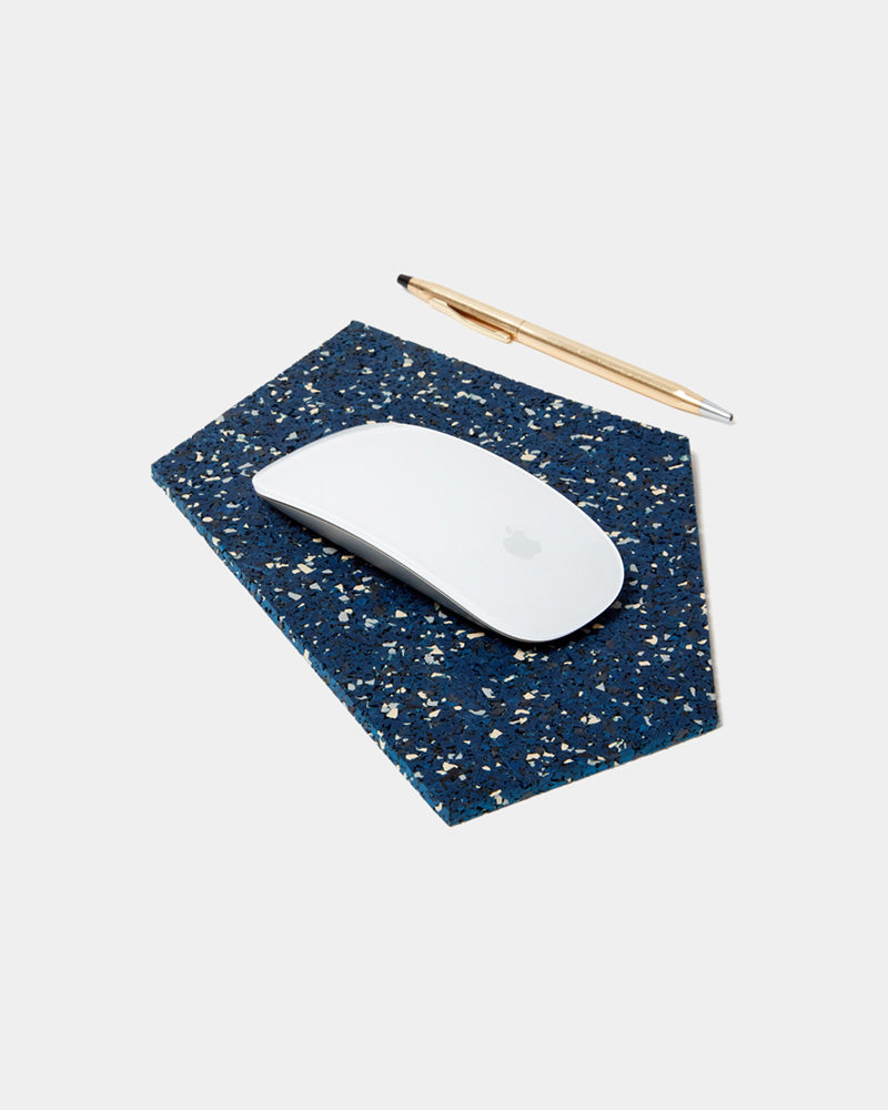 Geometric gem shaped speckled blue rubber mousepad with a white mouse and brass pen on white background.