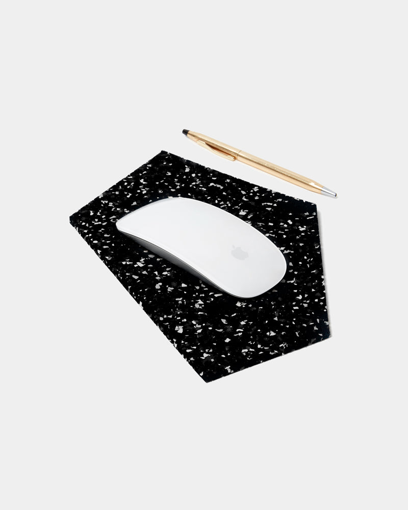 Geometric gem shaped speckled black rubber mousepad with a white mouse and brass pen on white background.
