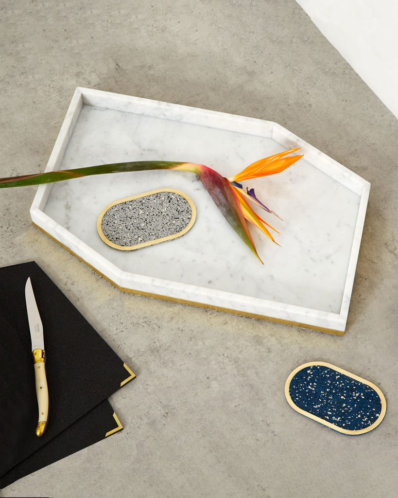 White geometric marble tray with speckled grey and blue brass ring coasters, orange flower and black rubber mats on concrete surface.