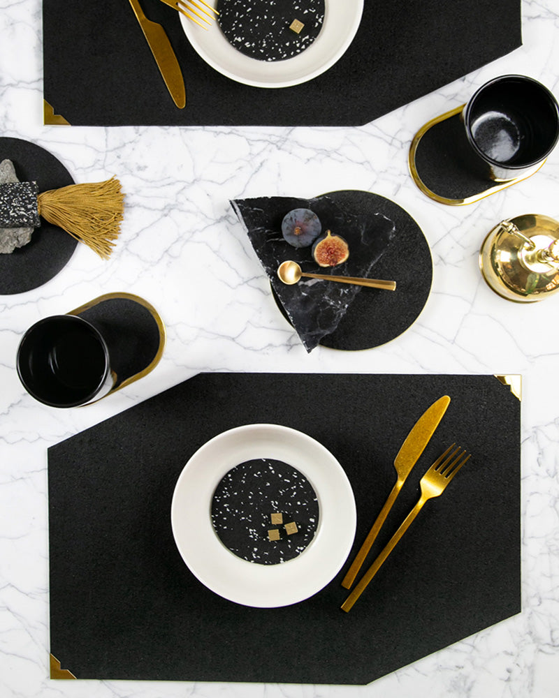 Black rubber table setting with geometric placemats, round trivets and brass ring coasters styled with brass cutlery, white dinnerware, black cups, black marble and fig.