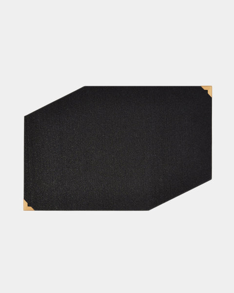 Black rubber geometric placemat with brass corners on white surface.
