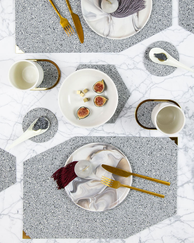 Speckled grey rubber table setting with geometric placemats, hexagon trivets, round coasters and brass ring coasters styled with brass cutlery, marbled dinnerware, rocks marble and figs.