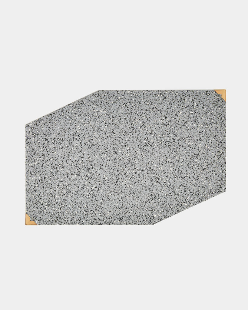 Speckled grey rubber geometric placemat with brass corners on white surface.