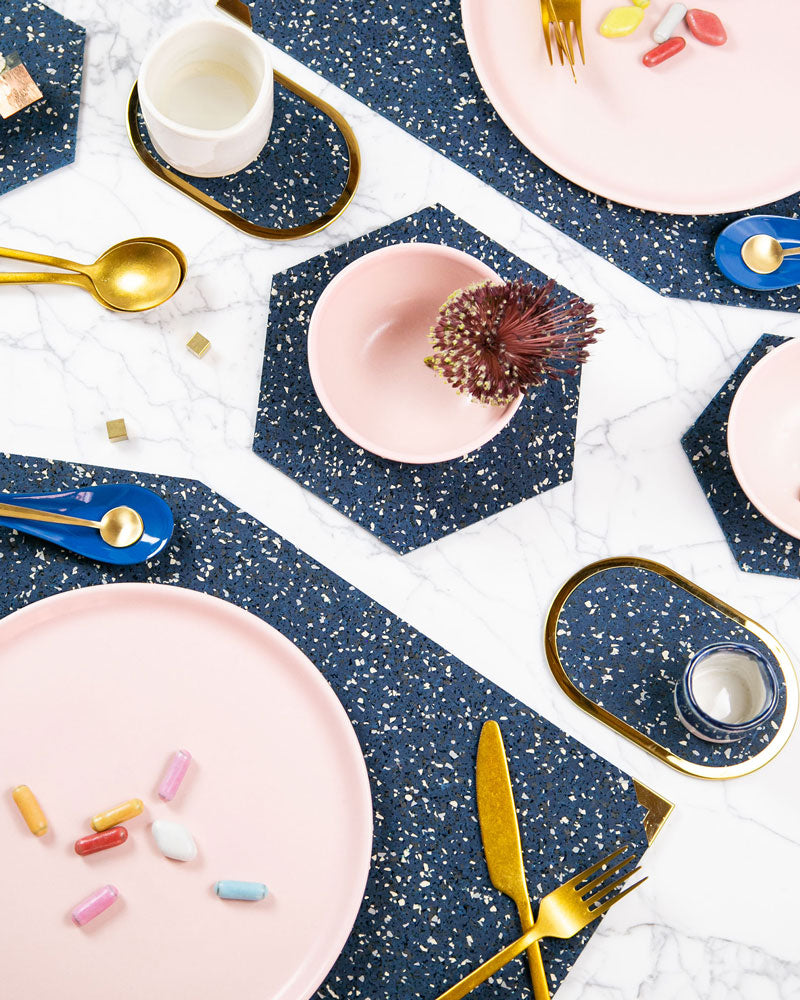 Speckled blue rubber table setting with geometric placemats, hexagon trivets and brass ring coasters styled with brass cutlery, pink dinnerware and coloured candy.