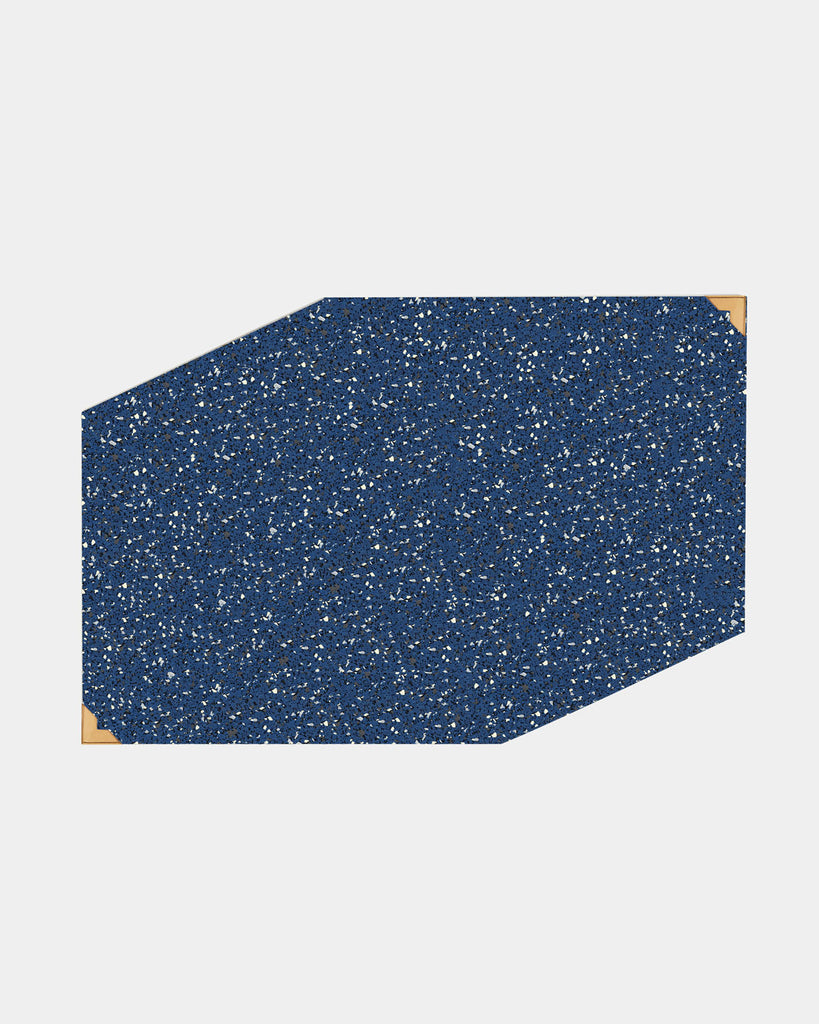 Speckled blue rubber geometric placemat with brass corners on white surface.