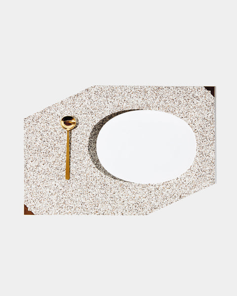 Speckled beige rubber geometric placemat with brass corners, white plate and brass spoon on white surface.