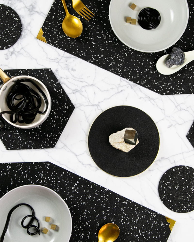 Speckled black rubber table setting with geometric placemats, hexagon trivet, black round trivet styled with brass cutlery, bowl with liquorish and rocks.