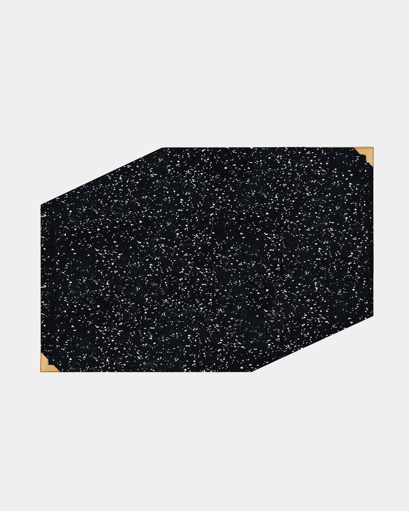 Speckled black rubber geometric placemat with brass corners on white surface.