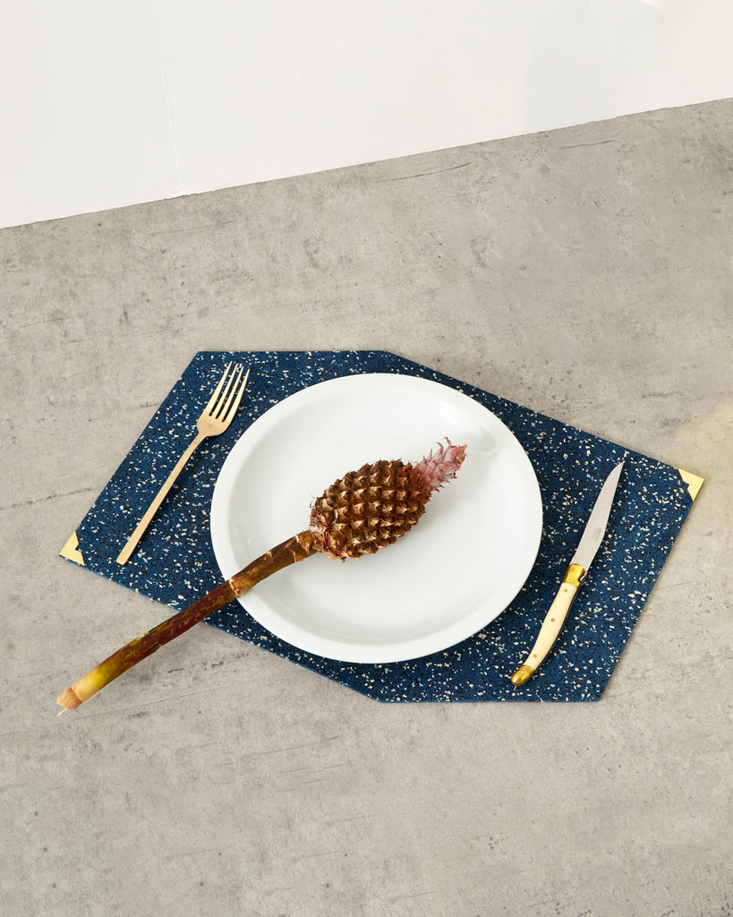 Blue speckled rubber placemat with brass corners on concrete surface. Fork, knife and a plate with small pineapple is placed on the place mat.