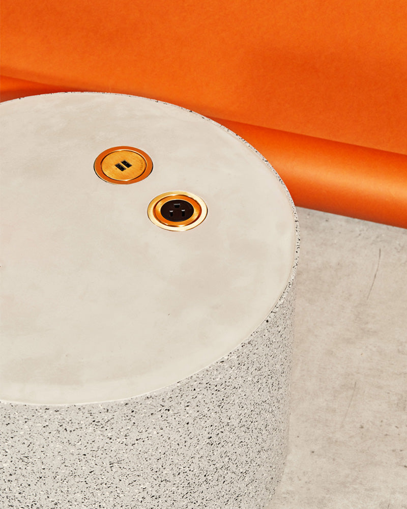 Detail image of round speckled gray rubber side table with brass power and USB outlet casted on its concrete surface.