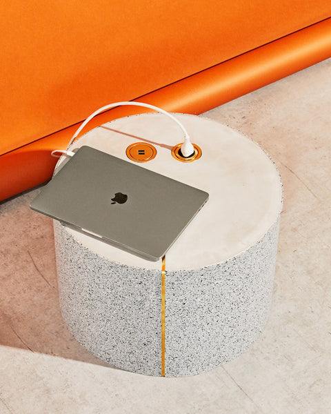 Round speckled gray rubber side table with brass power and USB outlet casted on its concrete surface. Gray laptop is on the table's surface and a white charge is plugged in to the power outlet.