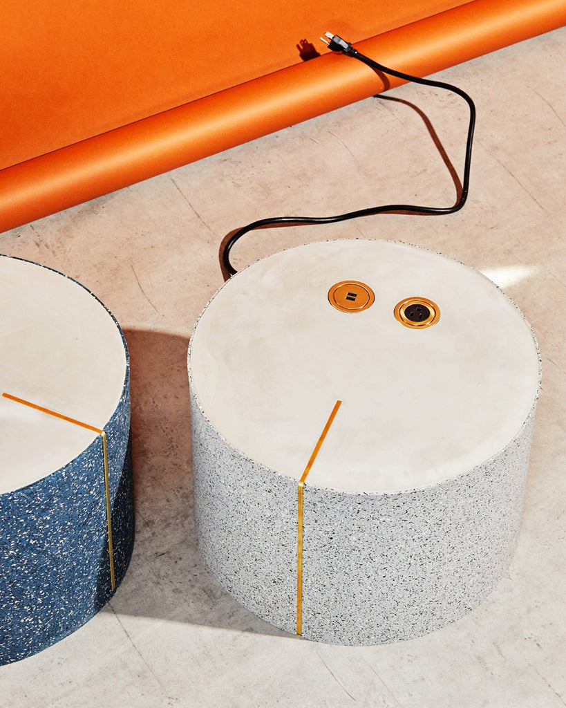 Round speckled gray rubber side table with brass power and USB outlet casted on its concrete surface. Next to it is a round speckled blue rubber side table with concrete surface and brass strip..