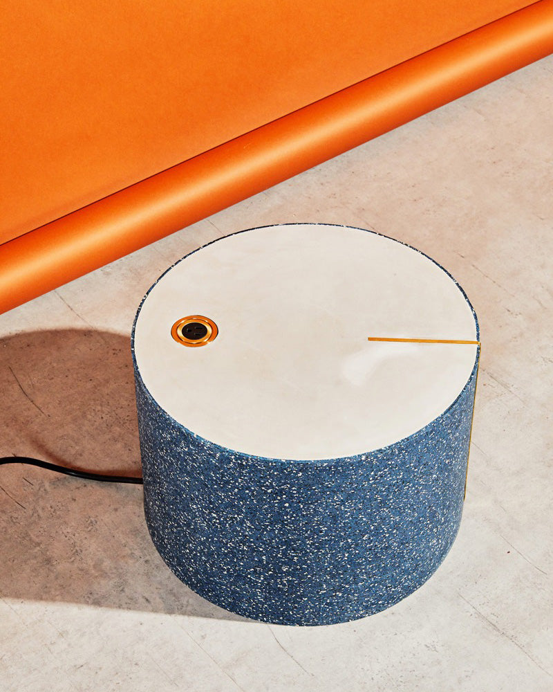 Round speckled blue rubber side table with brass power outlet casted on its concrete surface.