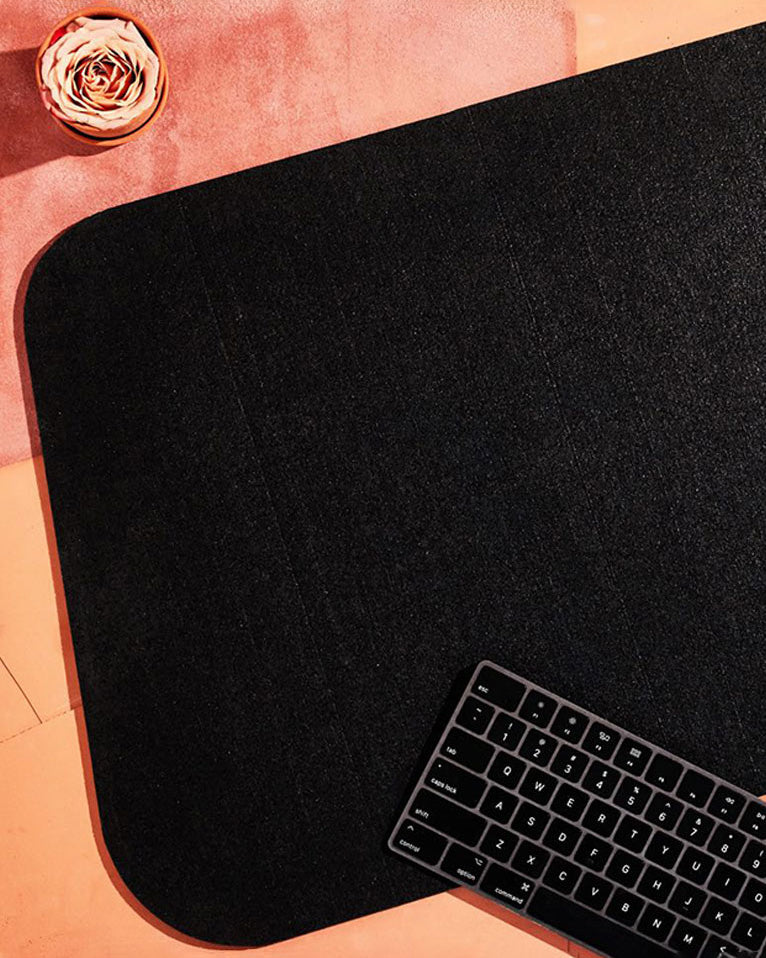 Black rubber desk mat, black keyboard and pink flower on terracotta surface.
