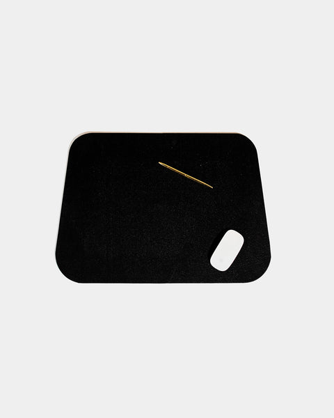 Rounded corner black rubber desk mat with brass pen and white mouse on white background.