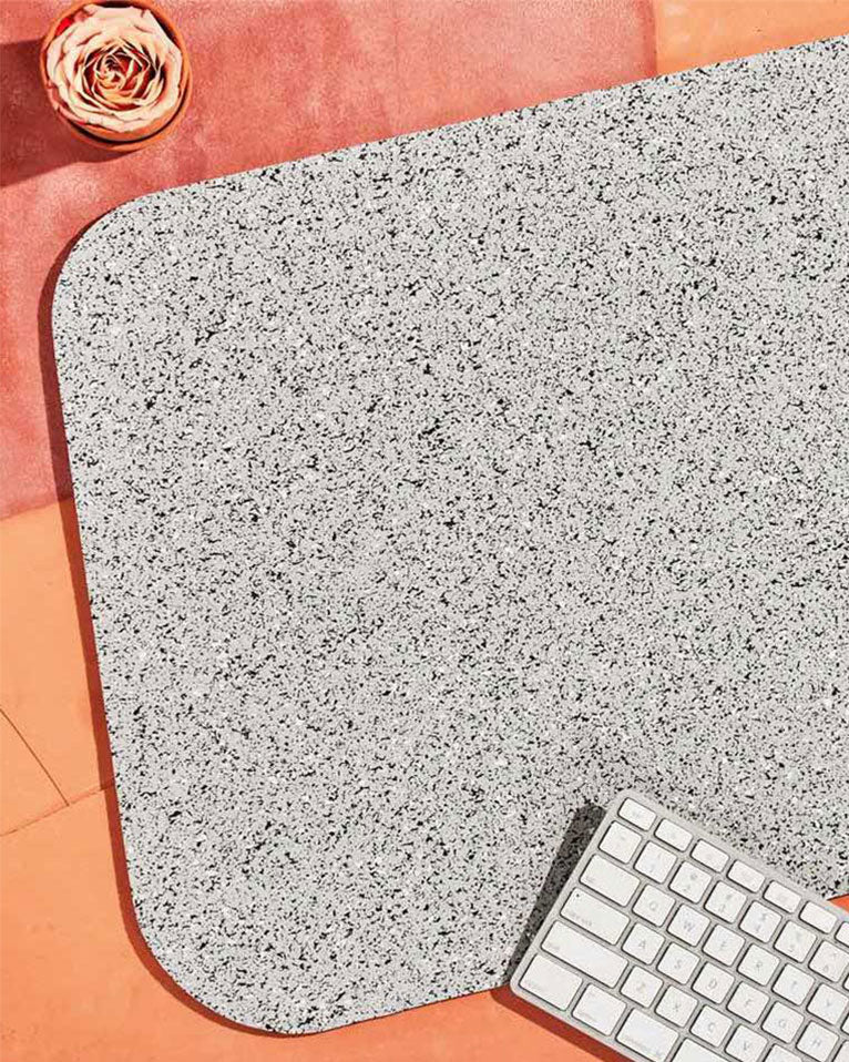 Speckled grey rubber desk mat, white keyboard and pink flower on terracotta surface.