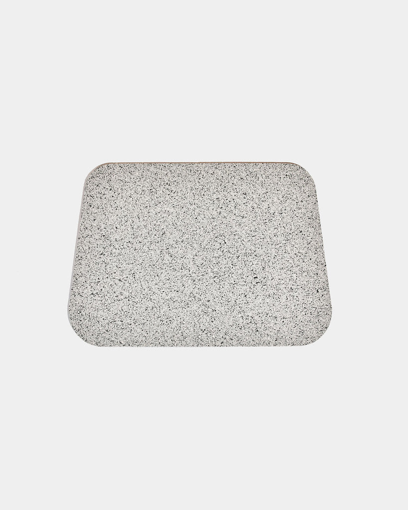 Rounded corner speckled grey rubber desk mat on white background.