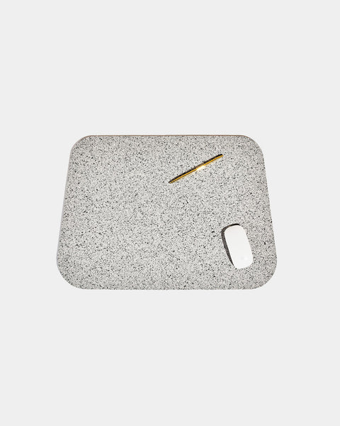 Rounded corner speckled grey rubber desk mat with brass pen and white mouse on white background.