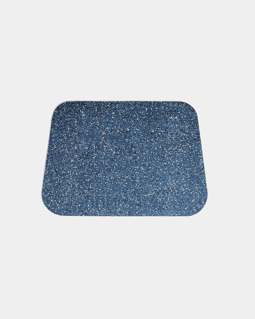 Rounded corner speckled blue rubber desk mat on white background.