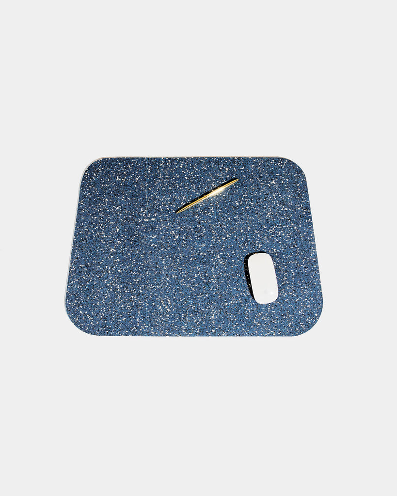 Rounded corner speckled blue rubber desk mat with brass pen and white mouse on white background.
