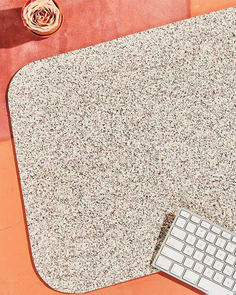 Speckled beige rubber desk mat, white keyboard and pink flower on terracotta surface.
